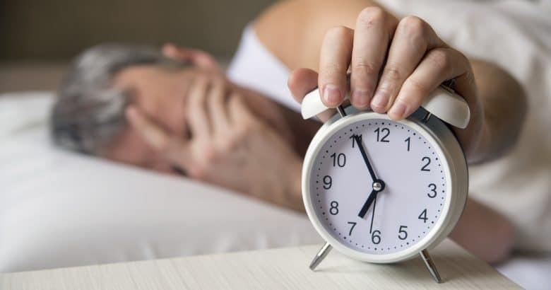 Remédio para Dormir | Homem deitado na cama desligando um despertador de manhã às 7 da manhã. Homem atraente dormindo em seu quarto. Homem irritado sendo despertado por um despertador em seu quarto