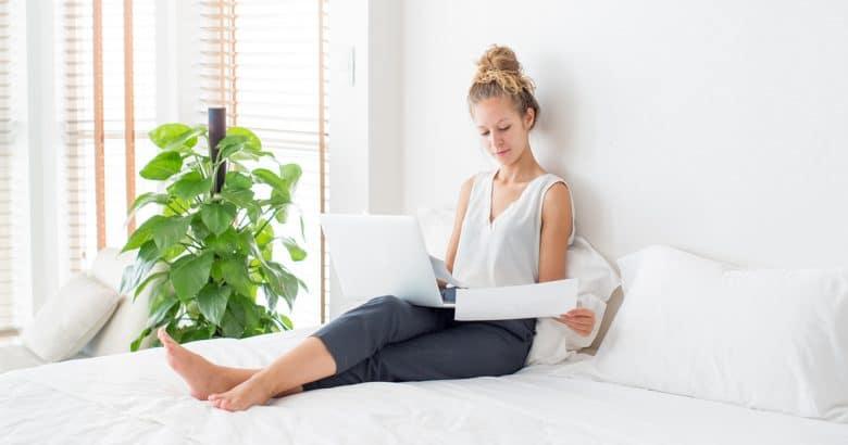 Mulher trabalhando no laptop e sentado na cama em casa | 5 Dicas Para Decorar o Quarto Com Plantas